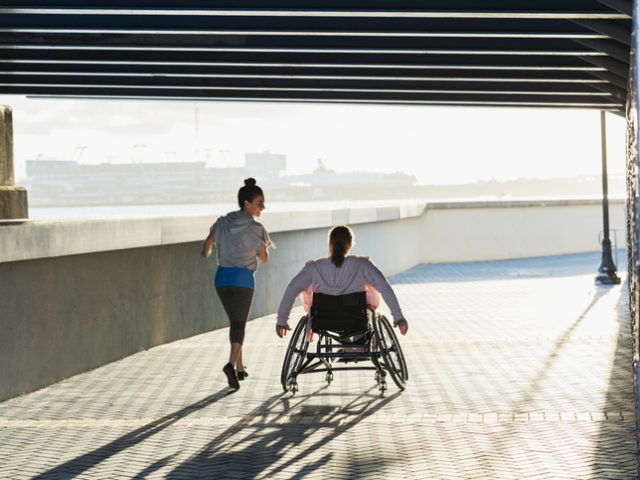 Rear view of two friends exercising along a city waterfront. The young woman in the wheelchair has spina bifida. Her friend jogging beside her and talking is a mid adult Hispanic woman in her 30s.