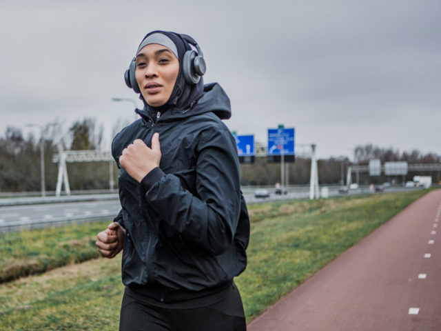 Beautiful Young Female Athlete wearing a sports hijab working out in an outdoor gym