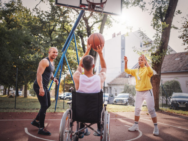 Disabled men playing basketball with friends