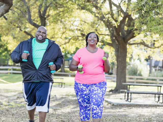 An African-American couple in the park, exercising together. They are lifting hand weights, power walking, smiling and moving toward the camera. They are both plus size models with large builds.